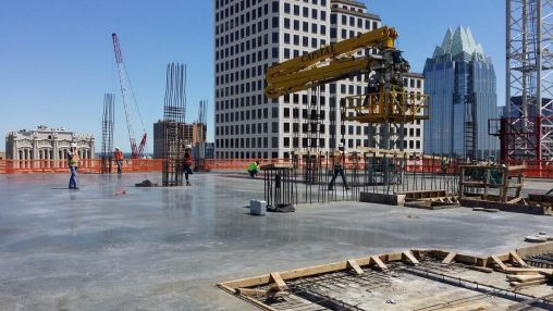 Freshly poured and finished concrete deck of the 14th floor – first pour (eastern third).  The concrete is pumped by a pumper truck from a continuous stream of trucks on 7th Street down to the Basement and up through the yellow pumper rig on the right.