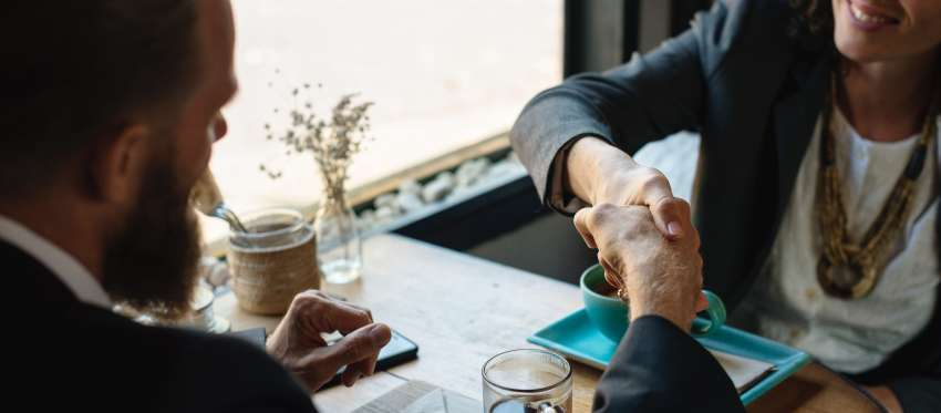 A man and woman shake hands over a table