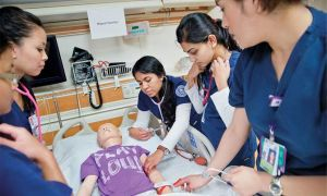 UT Arlington nursing students practice over a medical dummy in an hospital setting