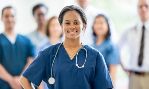 A smiling nurse in blue scrubs